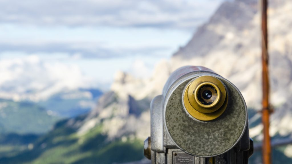 Binoculars with View Dolomites Mountains Representing Hacknowledge Monitoring Services